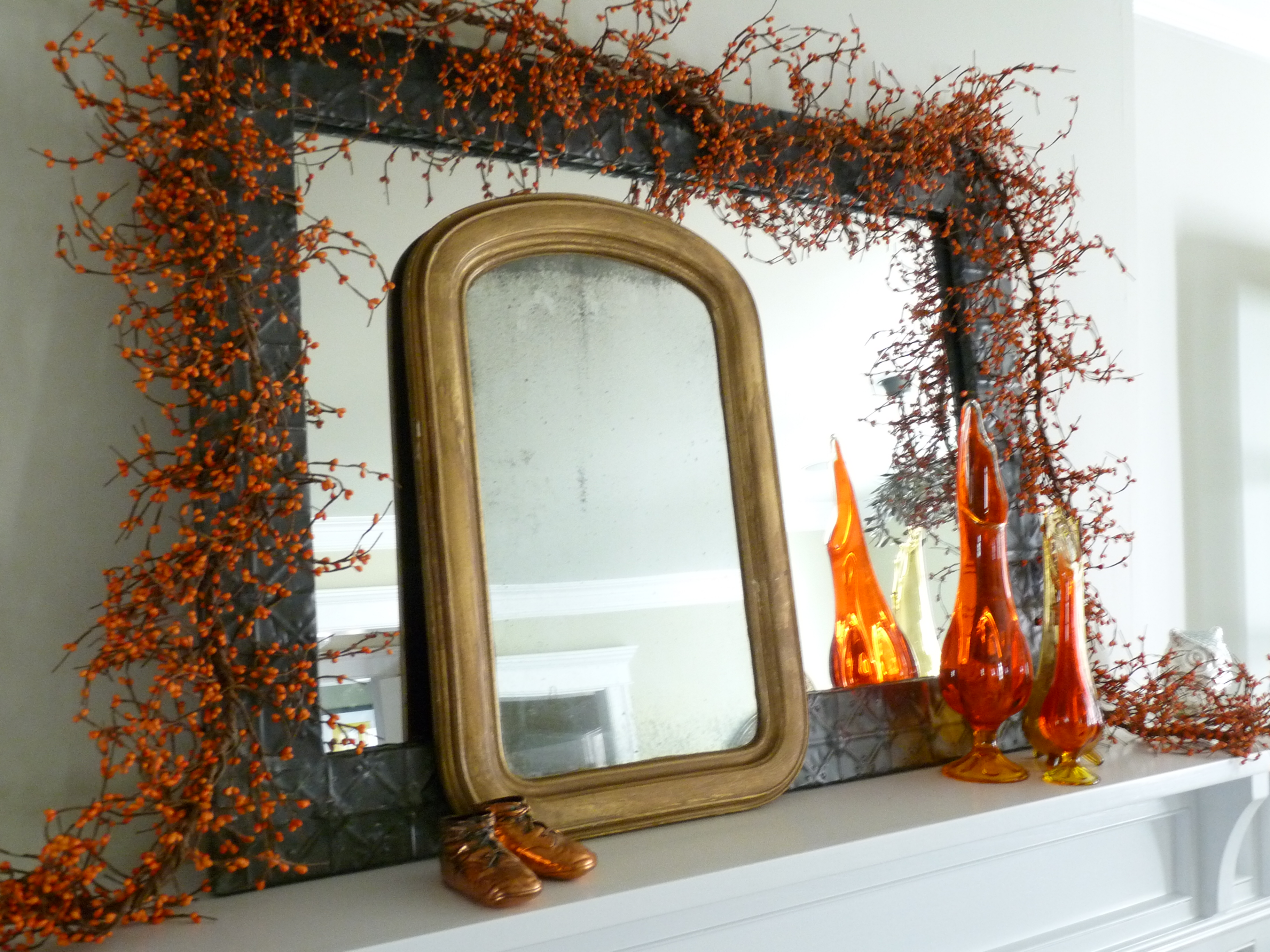 Fall mantel with orange berry garland and vintage mirrors kellyelko.com #falldecor #falldecorating #vintagedecor #fallmantel