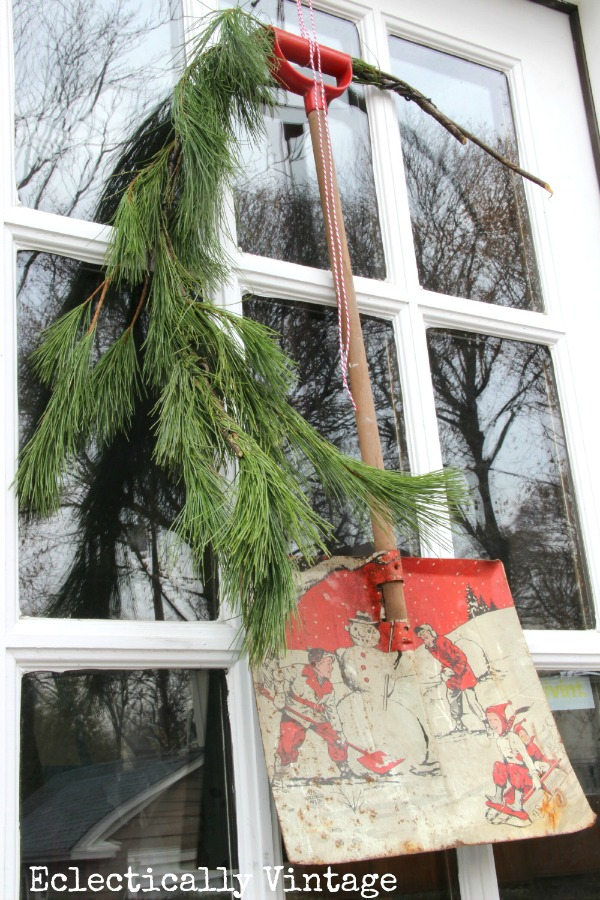 How fun is this vintage child's shovel used as a wreath on the door kellyelko.com #vintagechristmas #christmasdecor #christmasweath #vintage #wreaths #kellyelko