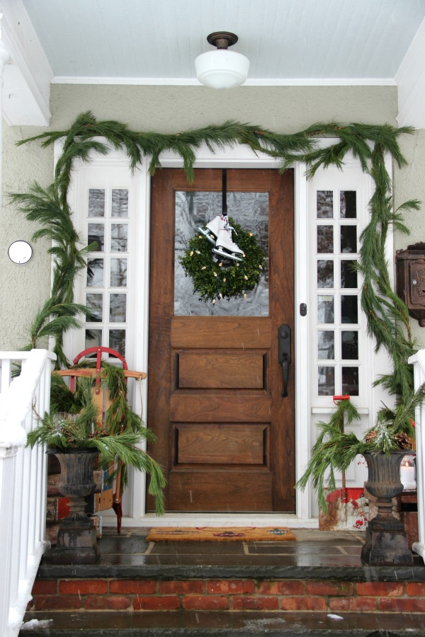 Beautiful Christmas porch - love the fresh garland around the door kellyelko.com