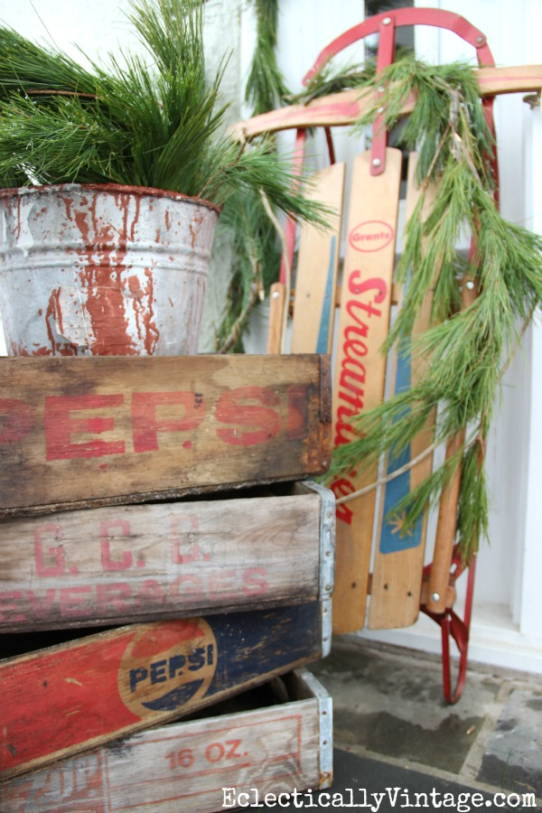 Love this stack of old wood soda crates used as a plant stand on this fun winter porch kellyelko.com #winterdecor #vintagechristmas #winterporch #christmasporch #vintagedecor #sodacrates #sled #kellyelko