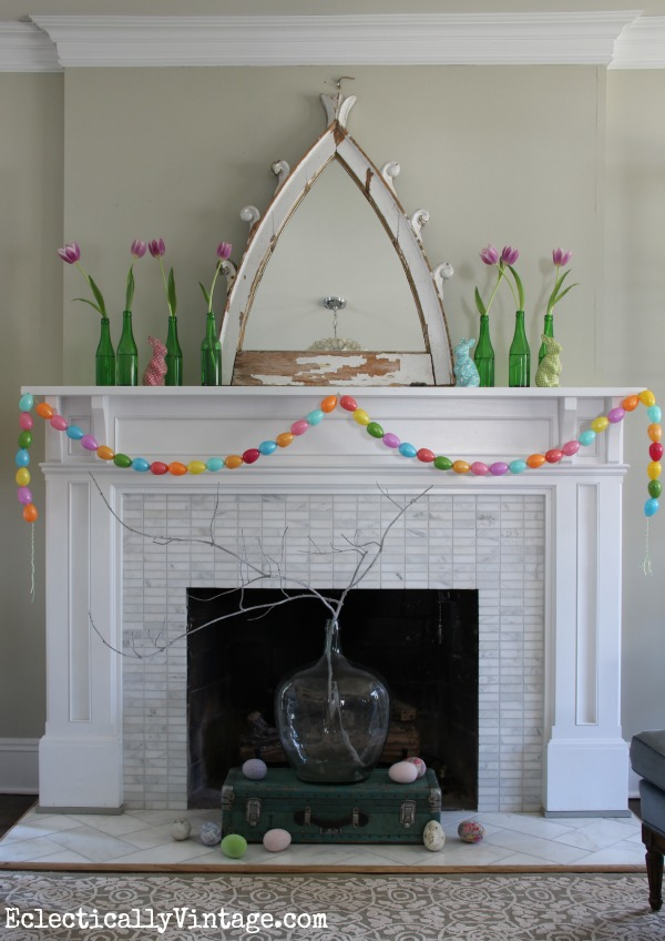 Fun spring mantel with DIY egg garland and vintage green glass bottles kellyelko.com
