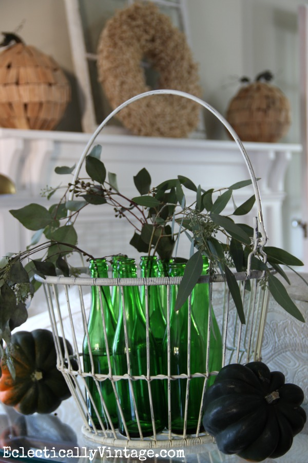 Vintage green glass bottles in a metal basket - gorgeous fall decorating ideas in this home kellyelko.com