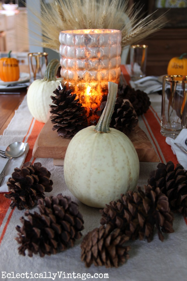 White pumpkins, pine cones, wheat and pops of orange create a gorgeous fall Thanksgiving table kellyelko.com
