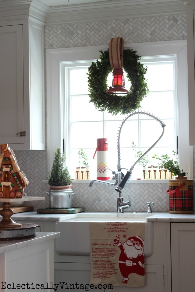 Festive Christmas kitchen window - love the old lantern in the wreath and the thermoses kellyelko.com