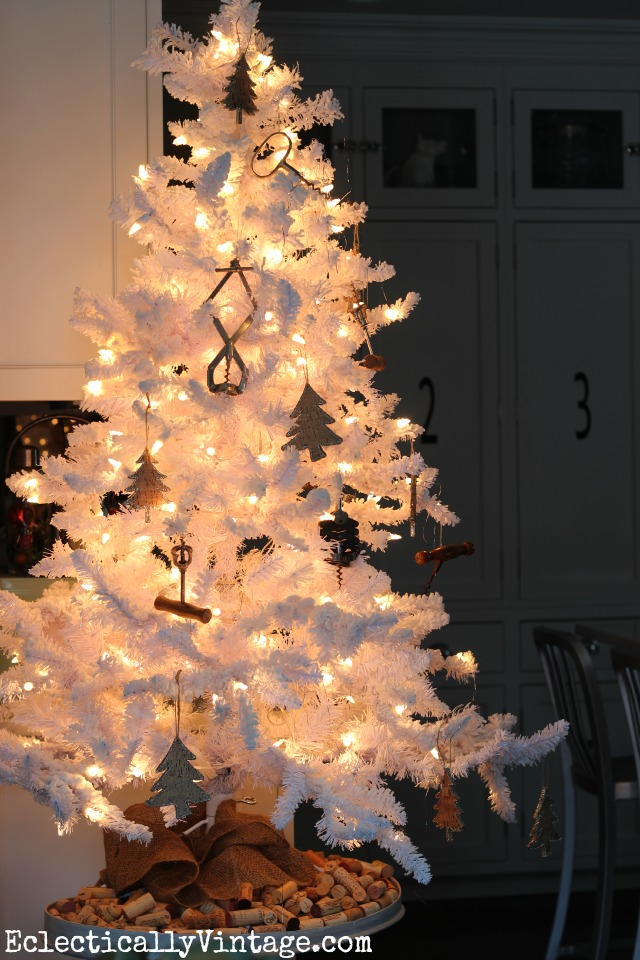 "White flocked Christmas tree - love the wine theme with old corkscrews and check out the ""tree skirt"" kellyelko.com"