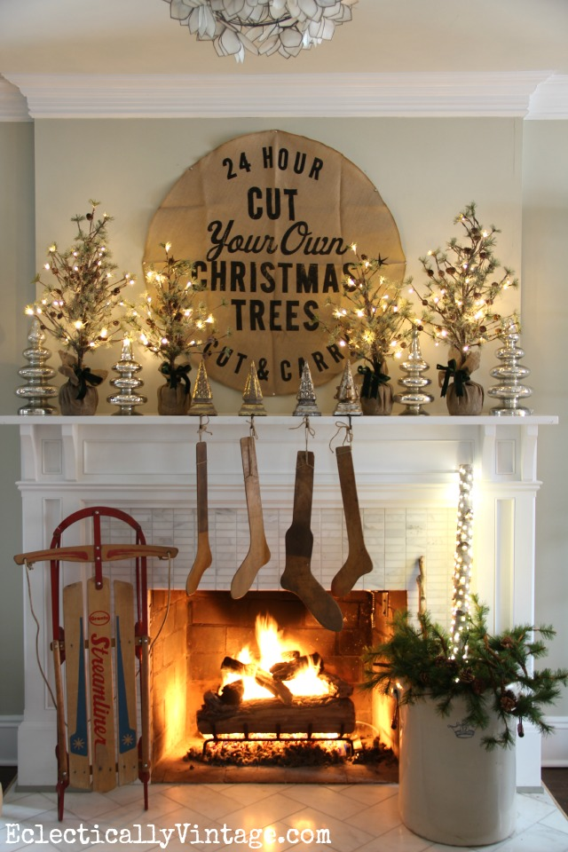 Christmas mantel - love the glowing mini trees, burlap sign and those vintage stocking stretchers! kellyelko.com