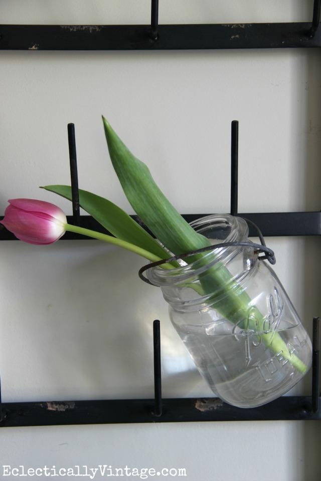 Cute idea - hang mason jars from a bottle drying rack to display flowers kellyelko.com #farmhouse #farmhousedecor #farmhousekitchen #platewall #vintagedecor #vintagekitchen #eclecticdecor #colorfuldecor #masonjars