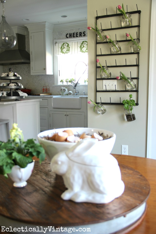 Love this kitchen and the huge bottle drying rack is so fun as a flower display plus see more creative display ideas and where to buy it! kellyelko.com #farmhouse #farmhousedecor #farmhousekitchen #platewall #vintagedecor #vintagekitchen #eclecticdecor #colorfuldecor #masonjars #springdecor