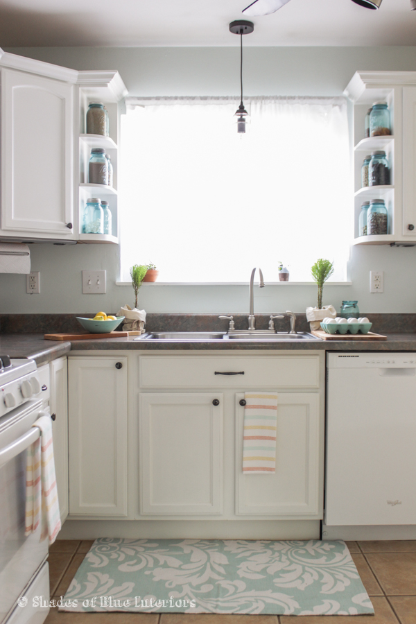 Love this charming white kitchen and the shelves filled with blue mason jars kellyelko.com