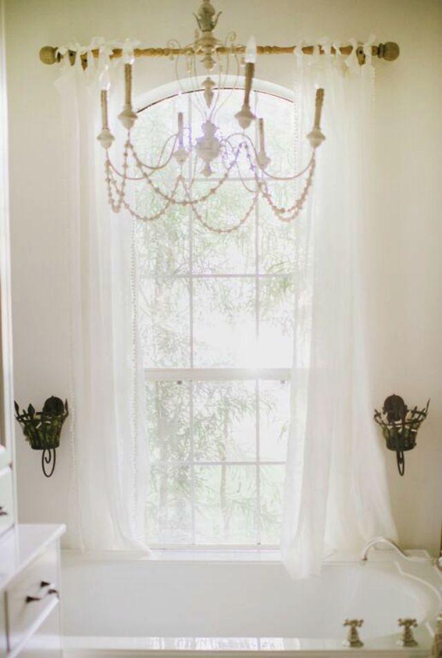 Love the glamorous chandelier over the bathtub
