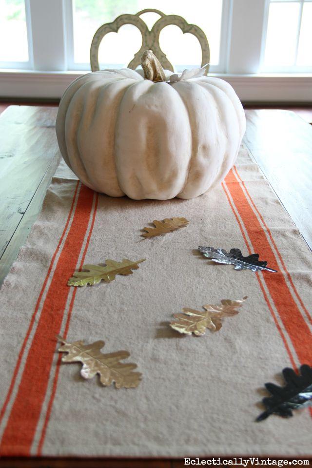 Love this fall centerpiece - a huge pumpkin, orange stripe table runner and DIY metal leaves kellyelko.com