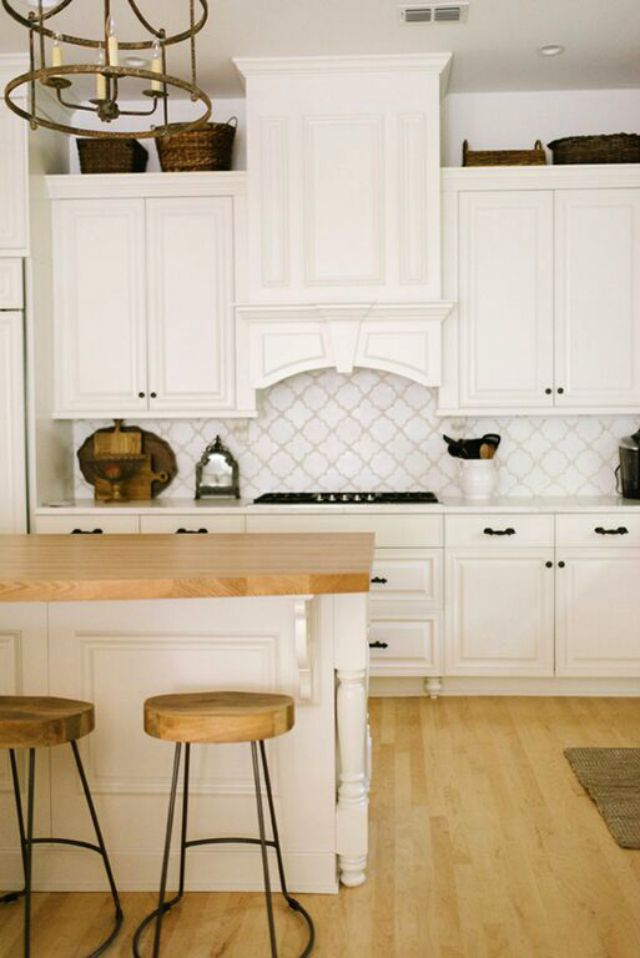 White kitchen with beautiful tile backsplash and butcher block counters