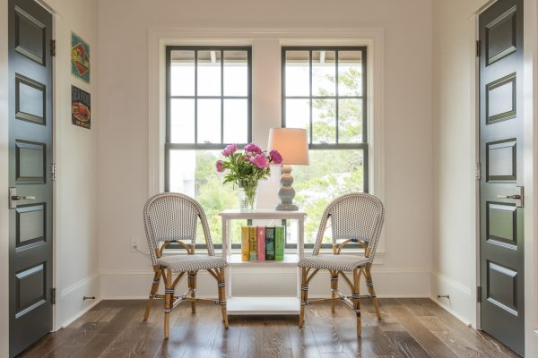 Love this pair of French bistro chairs and the black interior doors - tour this coastal home kellyelko.com