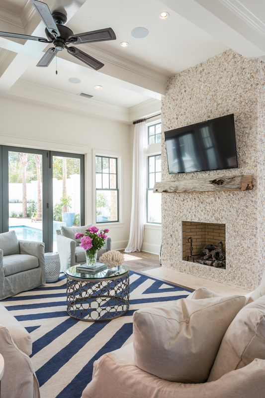 Love the graphic blue and white rug and the fireplace surround made of stucco and seashells! Tour the home kellyelko.com