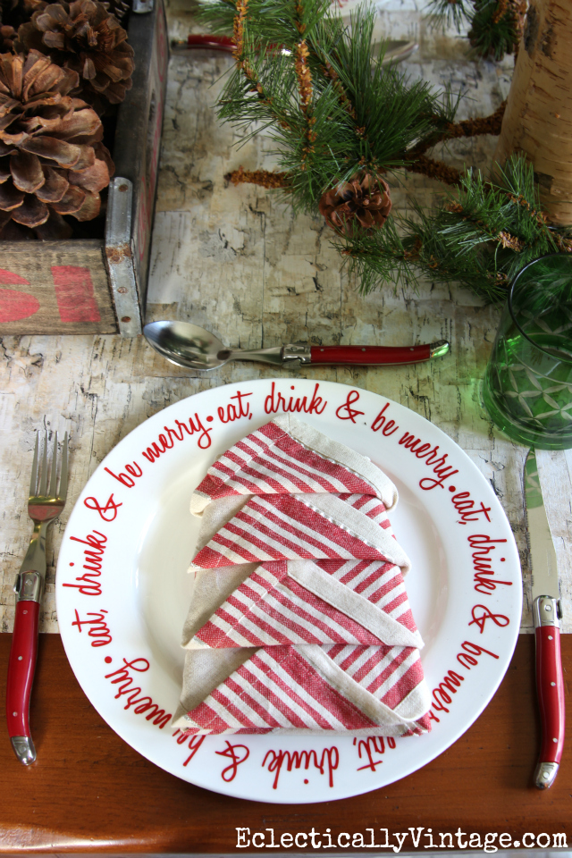 Rustic and whimsical Christmas tablescape. Love the napkin folded into the shape of a tree, birch bark table runner and red plates and cutlery kellyelko.com
