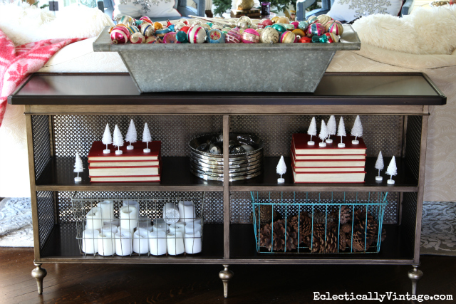 Console table shelves decked out for Christmas - love the huge zinc trough filled with vintage ornaments kellyelko.com
