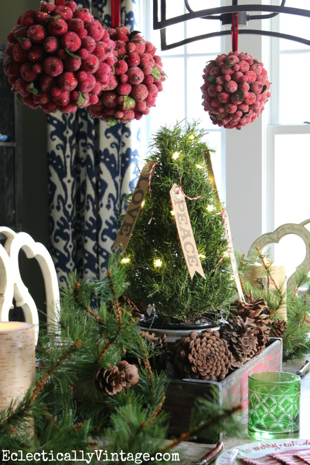 Rustic Christmas centerpiece - love the red kissing balls hanging above kellyelko.com