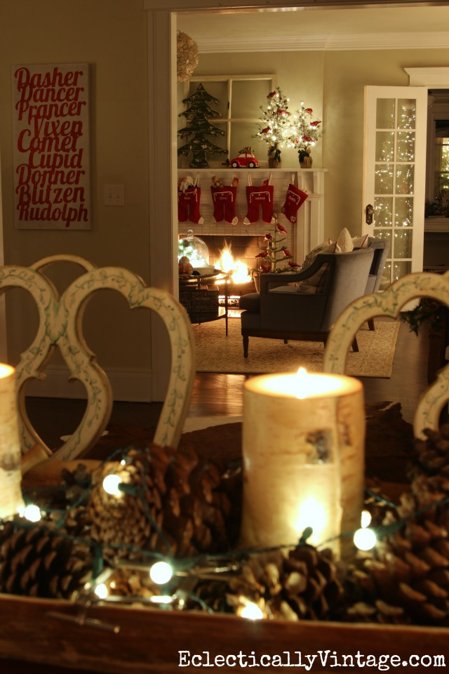 Festive Christmas home at night. Love the simple pinecone centerpiece with string lights kellyelko.com