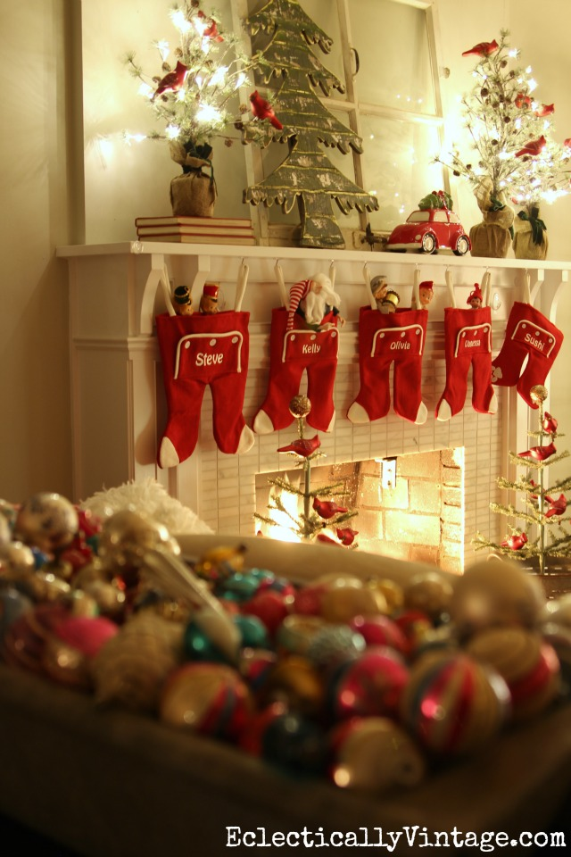 Love this festive Christmas mantel - the long john stockings and the sparkling trees with a flock of red cardinals kellyelko.com