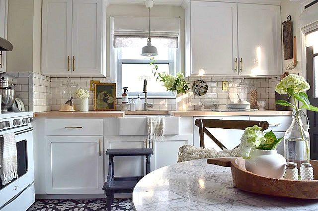 Love this small white kitchen with gold hardware and marble top table kellyelko.com
