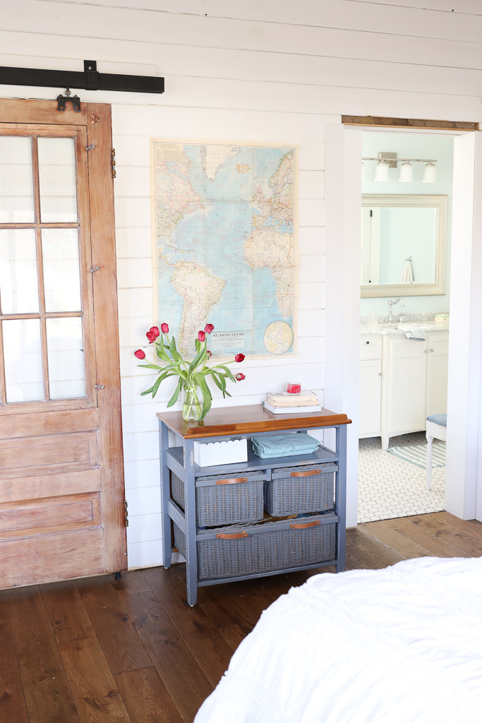 Love the sliding barn door and white planked walls in this cozy bedroom kellyelko.com