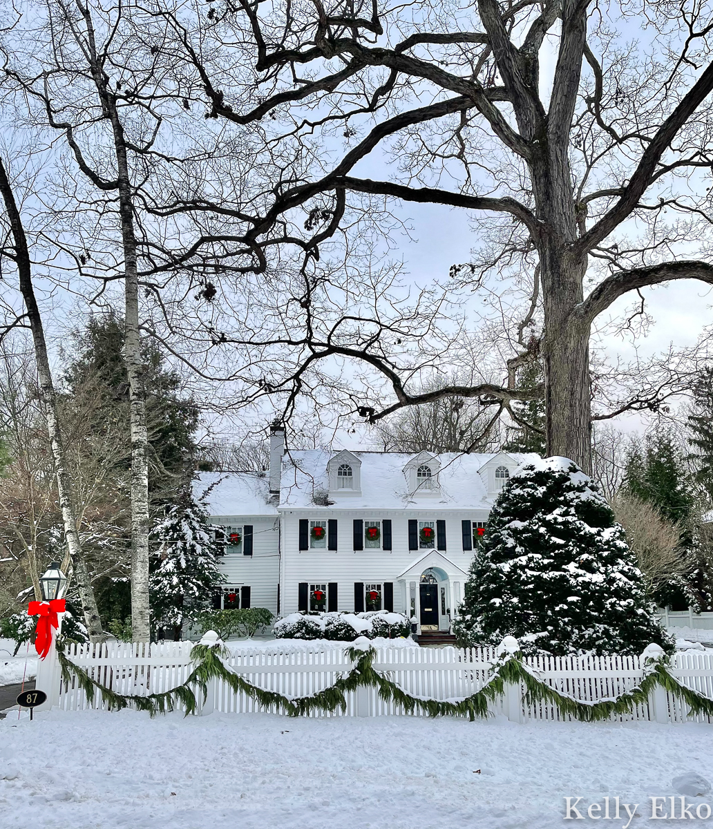 Love this classic white house with picket fence in the snow kellyelko.com