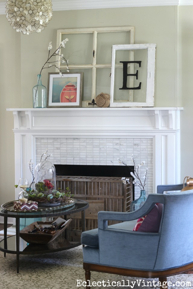 Spring mantel - love the old windows and the chicken coop fireplace cover kellyelko.com #spring #springdecor #springdecorating #springcrafts #hometour #housetour #eclectichome #farmhousedecor #fixerupperstyle #mantel #springmantel #vintagemantel #capiz #farmhousestyle #vintagedecor #vintagehome #kellyelko