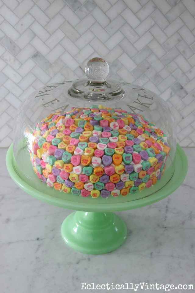 Love this conversation heart cake for Valentine's Day! How cute is that green cake stand too kellyelko.com