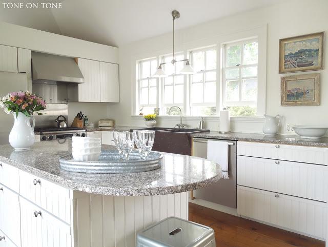 White kitchen - love the wall of windows and the nautical art kellyelko.com