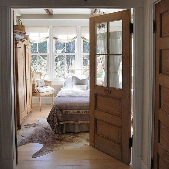 Love this guest bedroom - the old glass door is so charming kellyelko.com