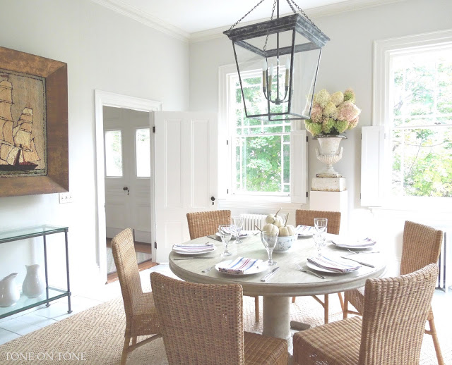 Love the round dining table, rattan chairs and huge lantern kellyelko.com