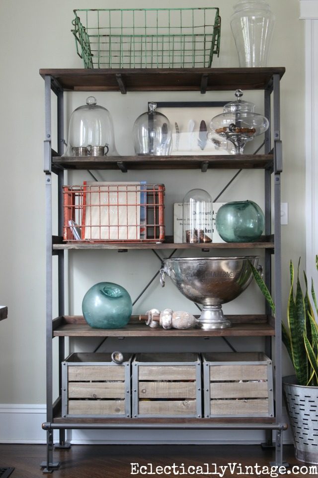 Open industrial shelf display - love the wire baskets and glass cloches kellyelko.com #spring #springdecor #springdecorating #springcrafts #hometour #housetour #eclectichome #farmhousedecor #fixerupperstyle #shelfie #farmhousestyle #vintagedecor #vintagehome #kellyelko #shelfstyling #industrialdecor