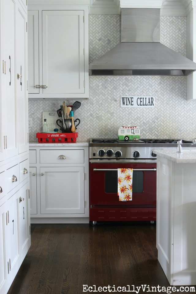 Love this white kitchen and carrara marble herringbone tile - the red stove really pops! kellyelko.com #spring #springdecor #springdecorating #springcrafts #hometour #housetour #eclectichome #farmhousedecor #fixerupperstyle #jadeite #farmhousestyle #vintagedecor #vintagehome #kellyelko #redstove #whitekitchen #backsplash #marbletile #herringbonetile #vintagedecor #vintagekitchen #kitchenreno