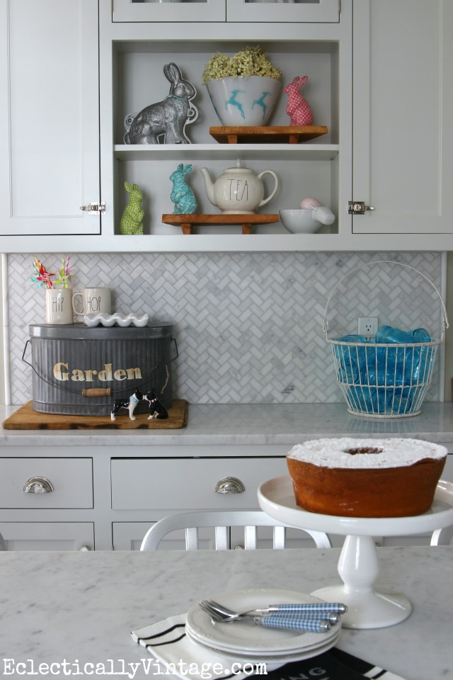 White spring kitchen - lots of fun display ideas and I love the galvanized garden pail kellyelko.com #spring #springdecor #springdecorating #springcrafts #hometour #housetour #eclectichome #farmhousedecor #fixerupperstyle #jadeite #farmhousestyle #vintagedecor #vintagehome #kellyelko #easterdecor #bunnies #whitekitchen #marblebacksplash #carraramarble