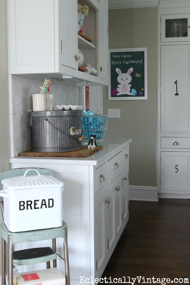 Spring kitchen - love the old step stool with the bread box kellyelko.com #spring #springdecor #springdecorating #springcrafts #hometour #housetour #eclectichome #farmhousedecor #fixerupperstyle #jadeite #farmhousestyle #vintagedecor #vintagehome #kellyelko #whitekitchen #breadbox #vintagedecor
