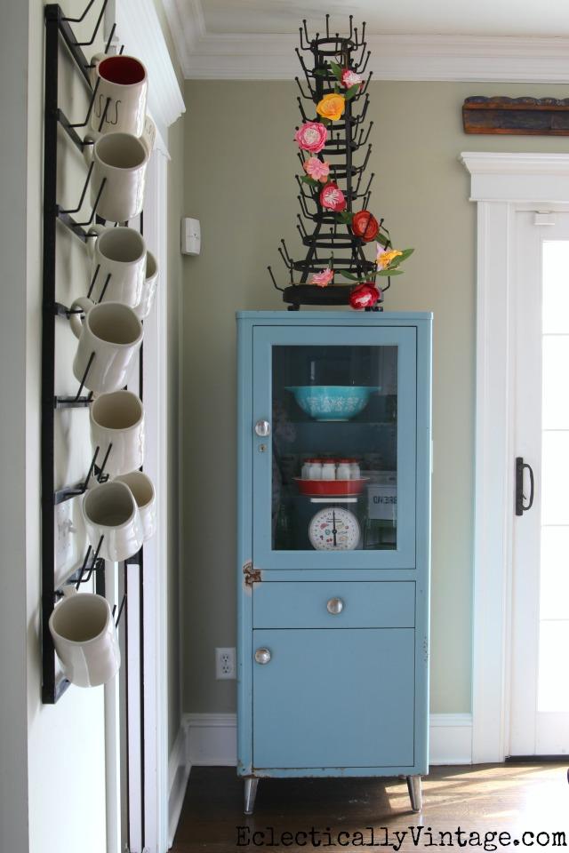 Vintage blue medical cabinet looks great in a kitchen kellyelko.com #bottlerack #springdecor #vintagedecor #aqua #eclecticdecor #kellyelko