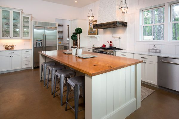 Love this white kitchen with stained concrete floors and wood counter and vertical planked walls kellyelko.com
