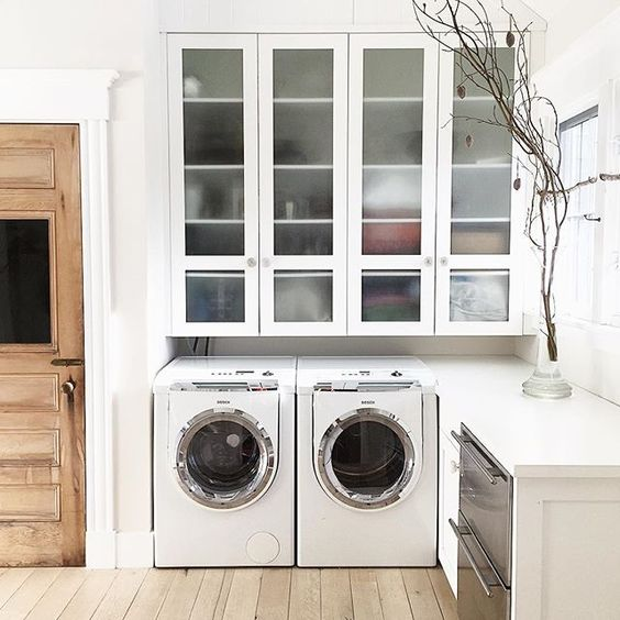 Beautiful laundry room with huge glass front cabinets kellyelko.com