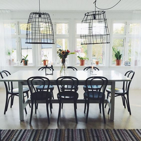 Love this modern and vintage dining room with black bentwood chairs and huge wire chandeliers! part of this amazing Swedish home tour kellyelko.com
