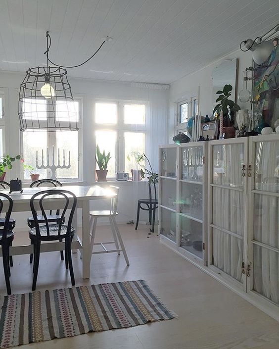love the built in glass cabinets in this white dining room with wire