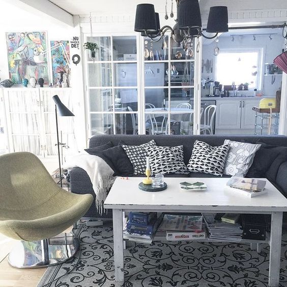 Modern furniture combines with a crystal chandelier and rustic coffee table kellyelko.com
