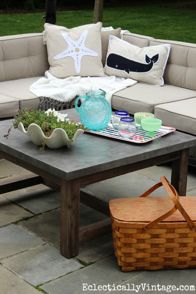 Love this huge concrete top outdoor coffee table and the sectional sofa with coastal pillows kellyelko.com