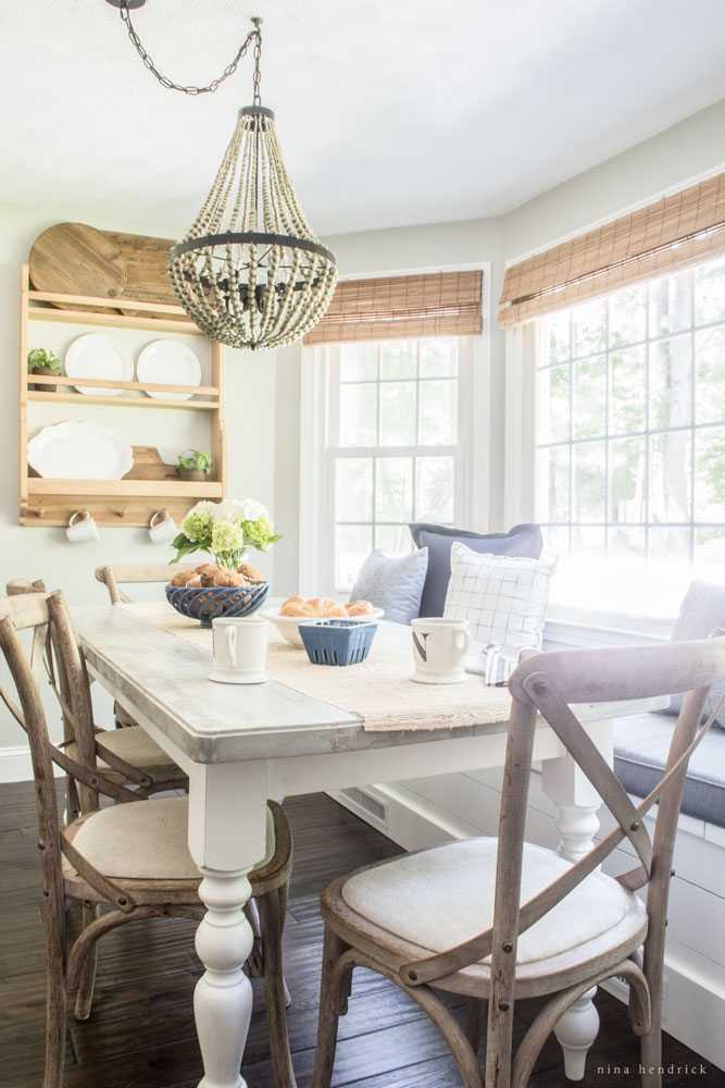 Love this farmhouse kitchen table with built in banquette mixed with x back chairs and beaded chandelier kellyelko.com