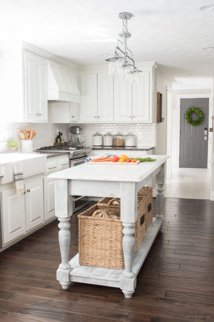 Farmhouse kitchen with painted white cabinets and DIY farmhouse island kellyelko.com