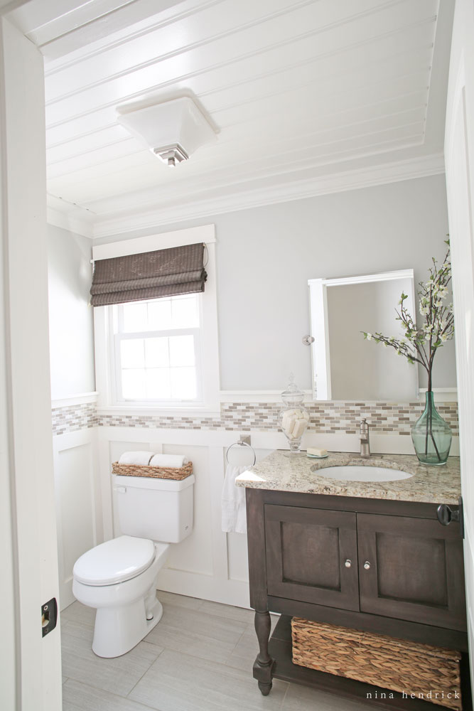 Love the details in this small powder room - the bead board ceiling and tile trim kellyelko.com