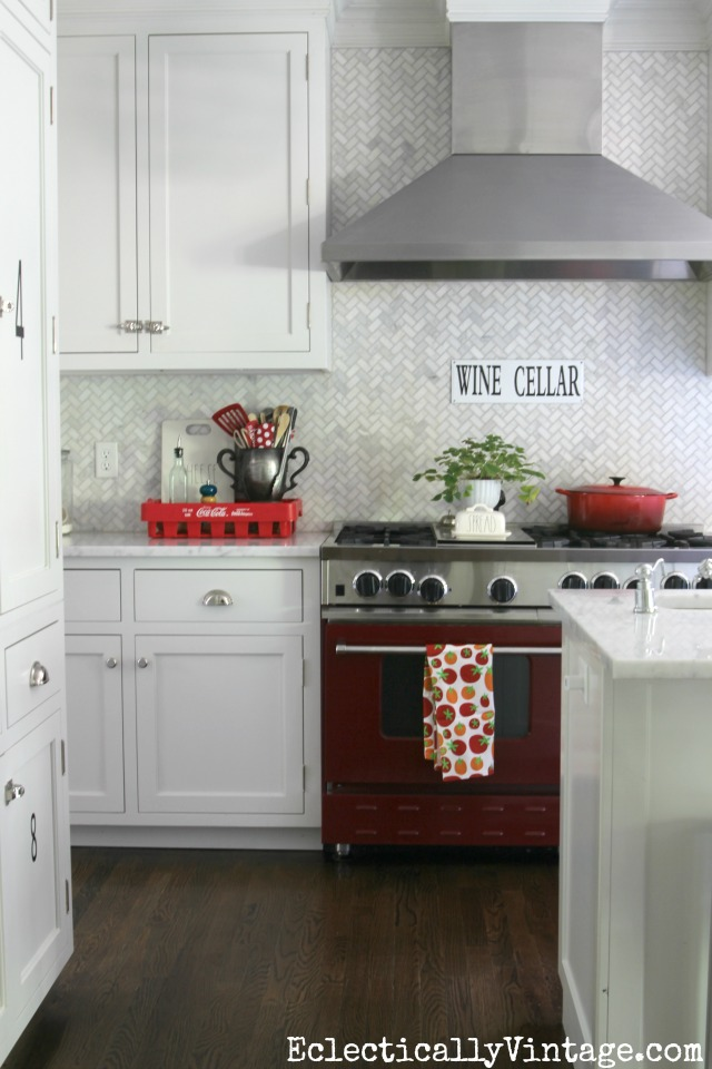 Red stove with carrara marble herringbone backsplash kellyelko.com