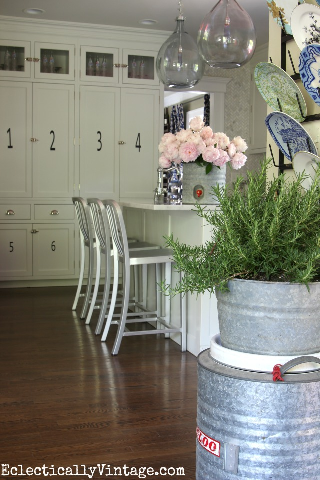Love this white kitchen that gets personality from vintage finds like these galvanized vintage coolers used as vases! kellyelko.com