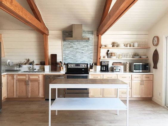 Modern kitchen with ceiling beams, shiplap walls and a huge stand alone island kellyelko.com