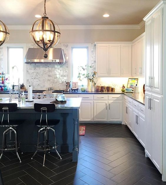 Love this white kitchen with black herringbone tile and the statement lighting! kellyelko.com