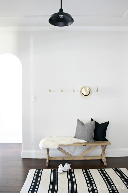 Love the simplicity of a black and white foyer with hooks for storage kellyelko.com